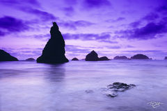 oregon coast, Bandon, Bandon Beach, haystacks, rocky coastline, sunset on the pacific ocean, silhouette, rocks silhouetted by the sun, purple sky, purple clouds, lavender sky, sea stack