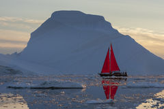 kangia icefjord; ice; iceberg; late day light; icefjord; ship; sailboat; schooner; sails; red sails, scarlet sails, reflection, backlit, silhouette