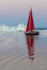 Kangia icefjord; ice; iceberg; disko bay; predawn; dusk; eventide; twilight; icefjord; ship; sailboat; sailing; red sails; schooner; scarlet sails; swizzle, reflection, pastel sky; pink; blue; scarlet