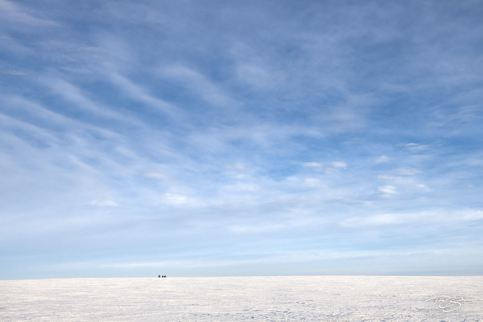 Silos in the great expanse of the Winter prairie