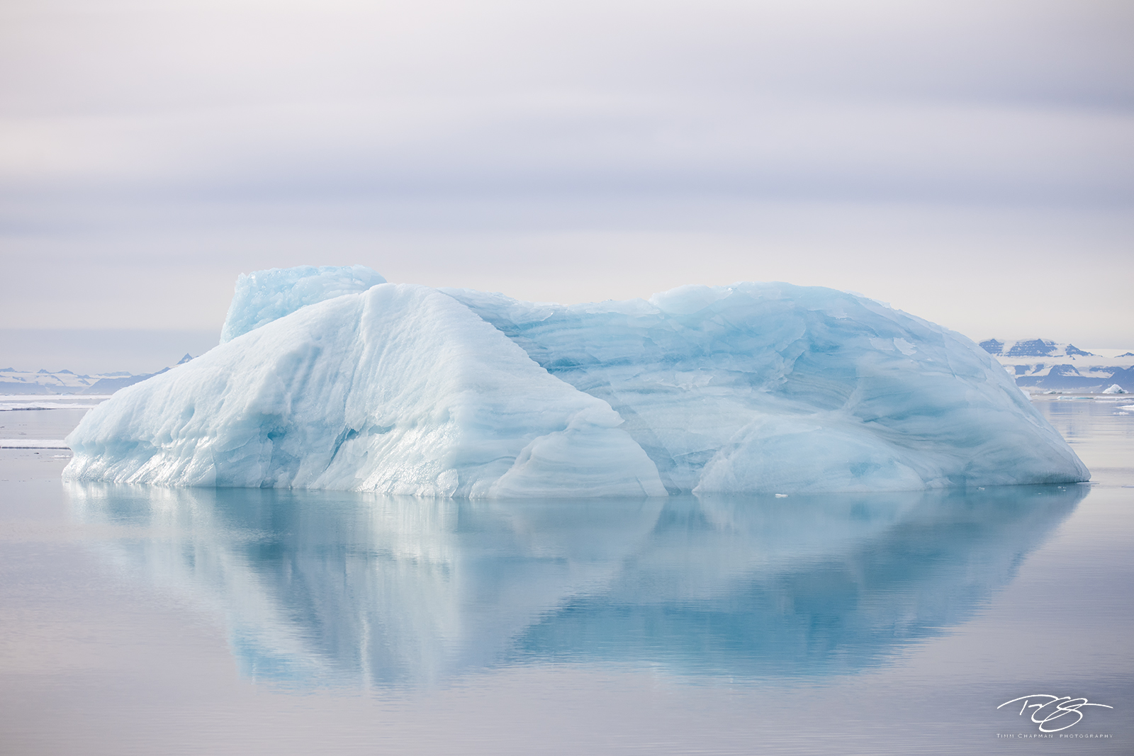 A silent hush washes over an iceberg on a still morning in the Scoresbysund of East Greenland