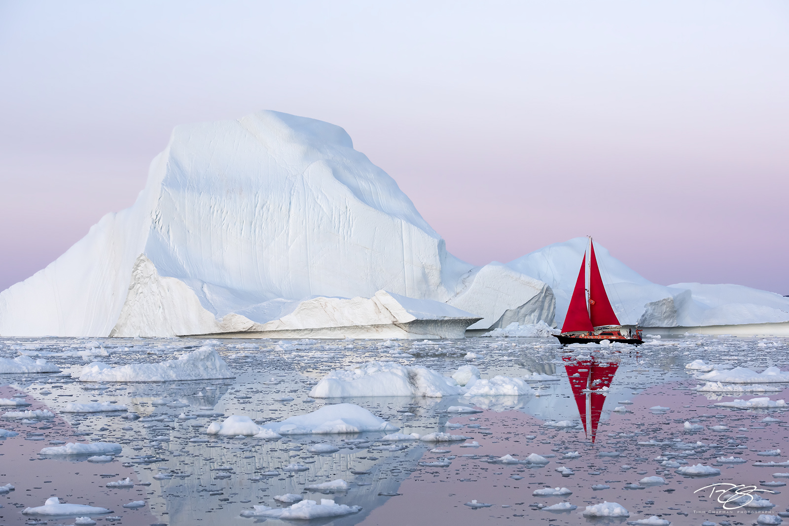 ice; iceberg; dusk; twilight; eventide; icefjord; ship; sailboat; schooner; sails; red sails; scarlet sails, reflection; pink sky; pastel sky; alpenglow