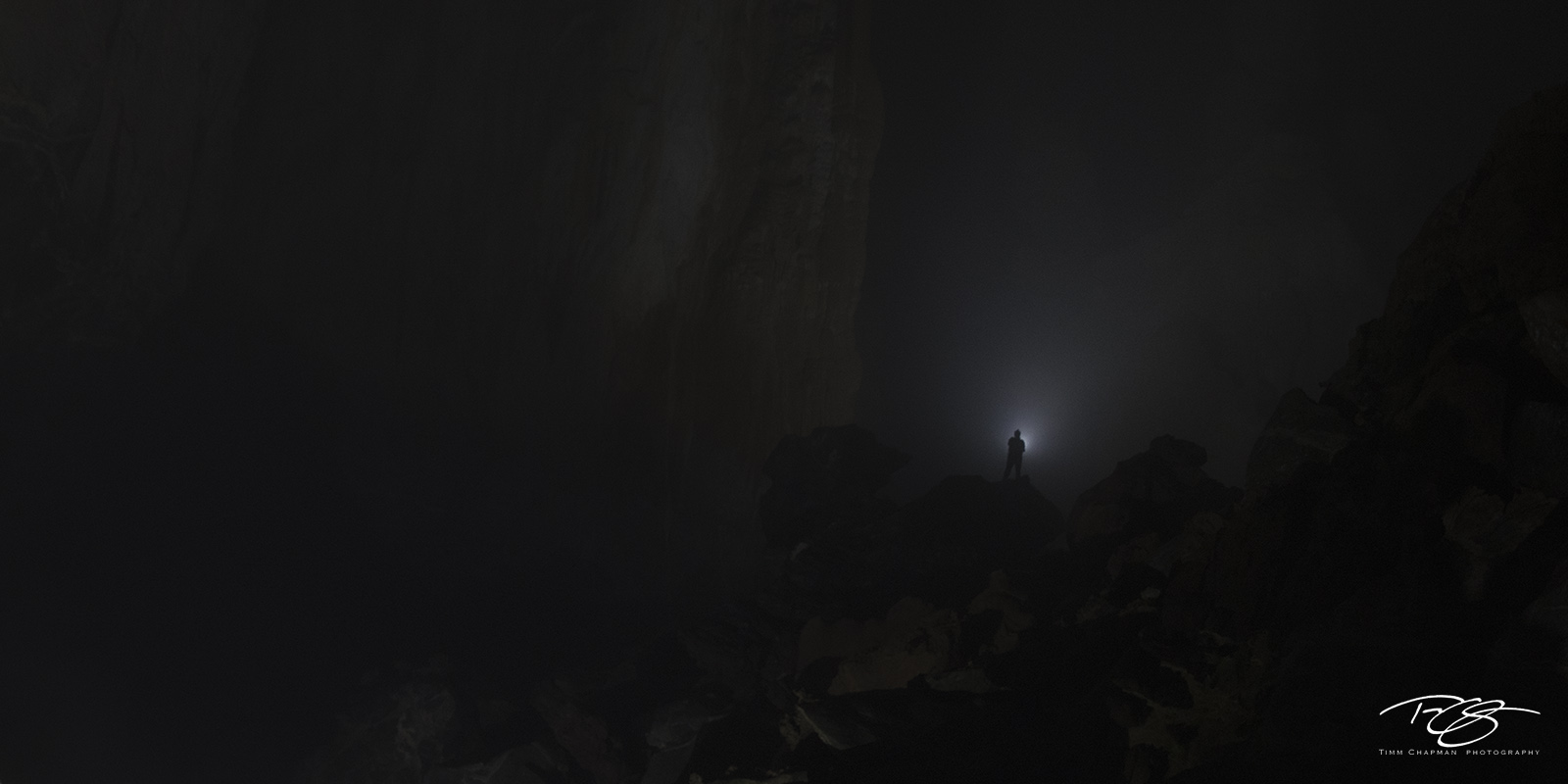 A lone explorer is dwarfed by the darkness inside the colossal Hang Son Ðoòng