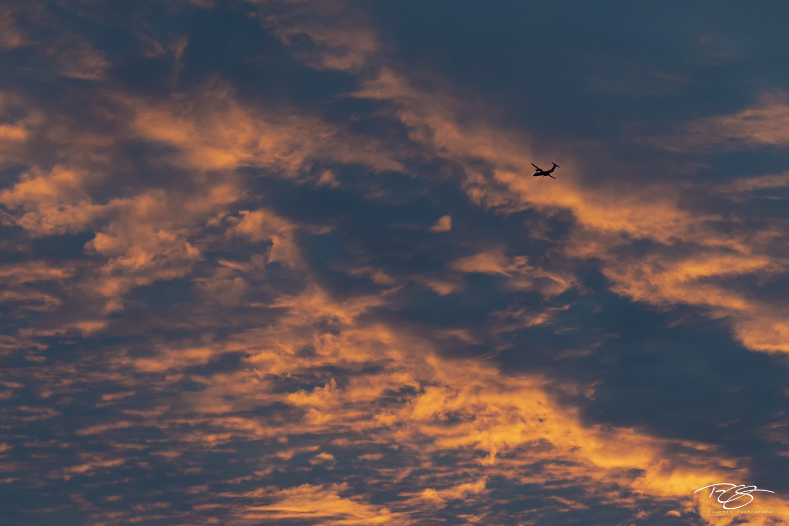 clouds; sky; fiery; colourful; colorful; cloudy; airplane; aircraft; flying; silhouette; flight; aircraft in flight; plane; plane in flight