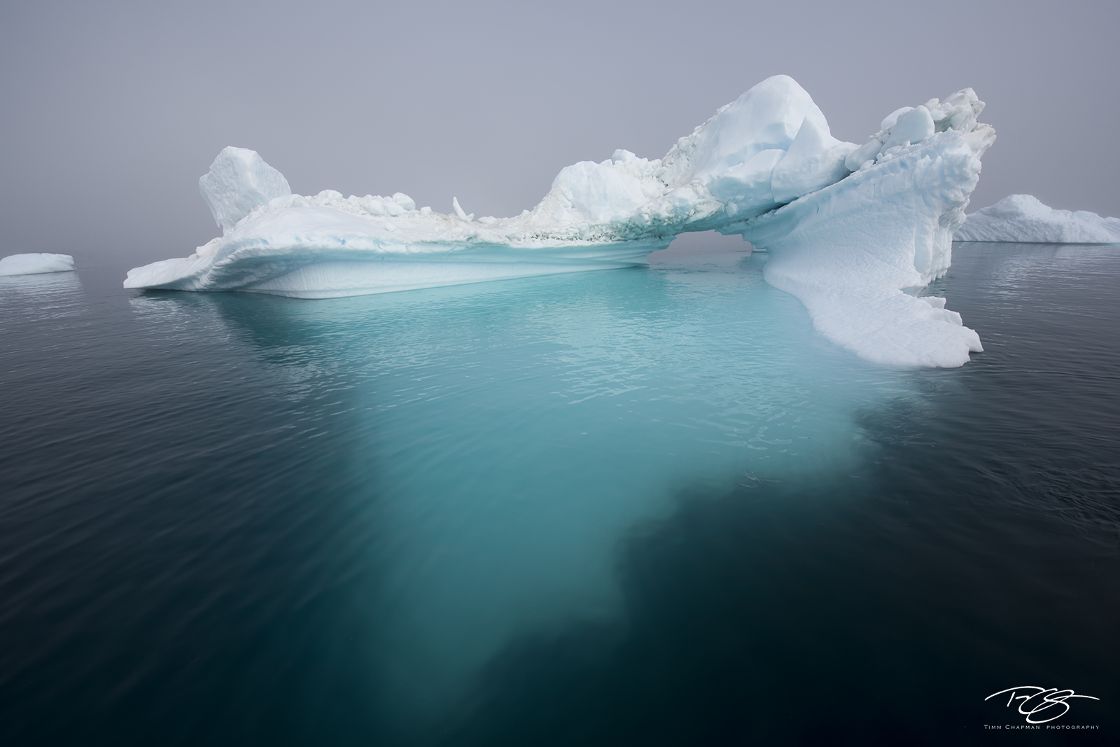 A massive iceberg emerges from thick fog cloaking Greenland's Disko Bay