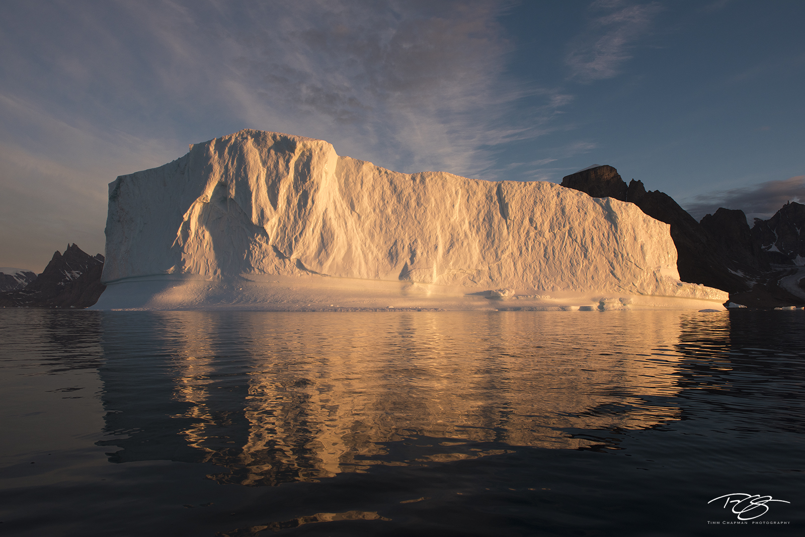 A massive iceberg warms with the first rays of the day's sun in East Greenland
