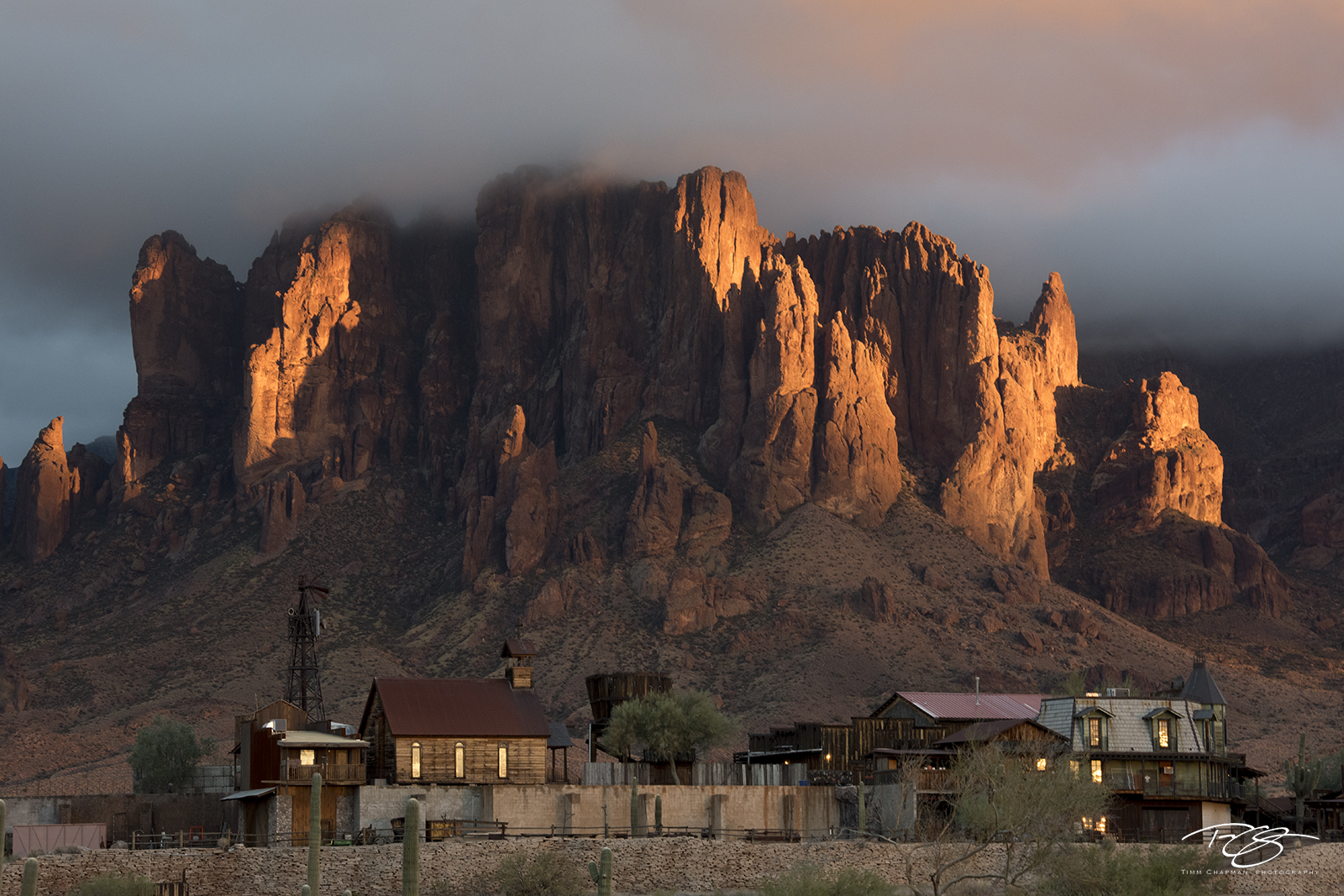 Superstition Mountain glows with the last liight of day as it watches over the old western town of Goldfield