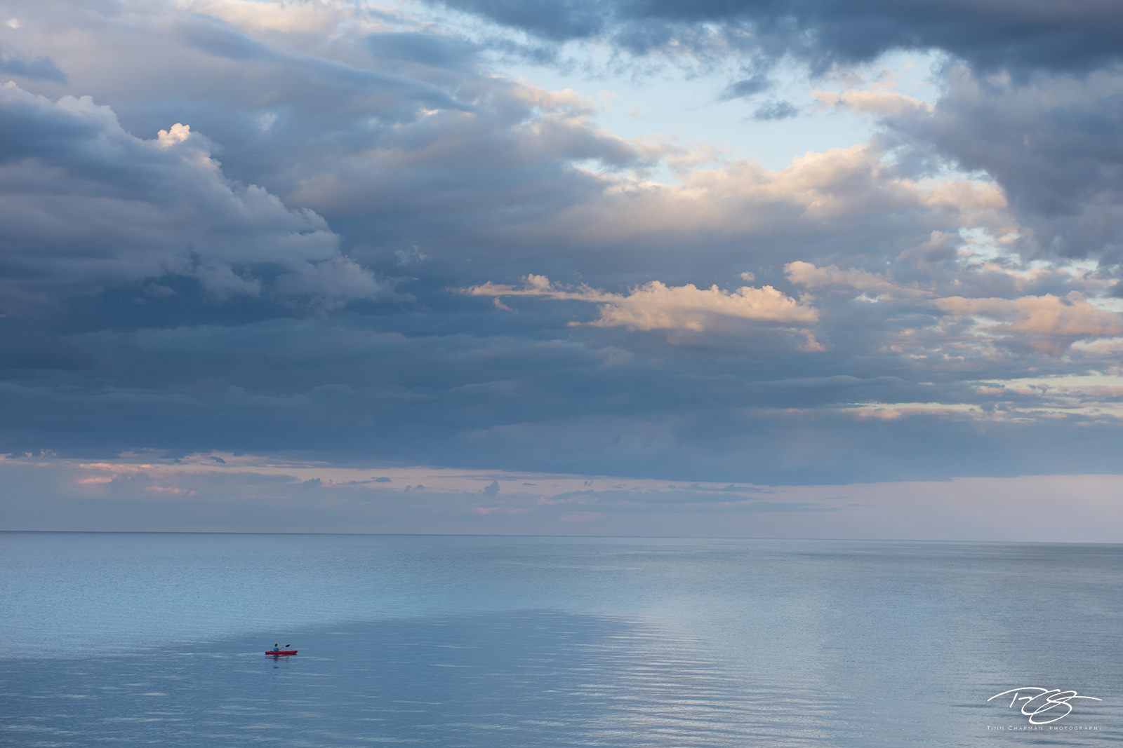 A solitary kayaker forges out into the expanse of the Great Big Sea.