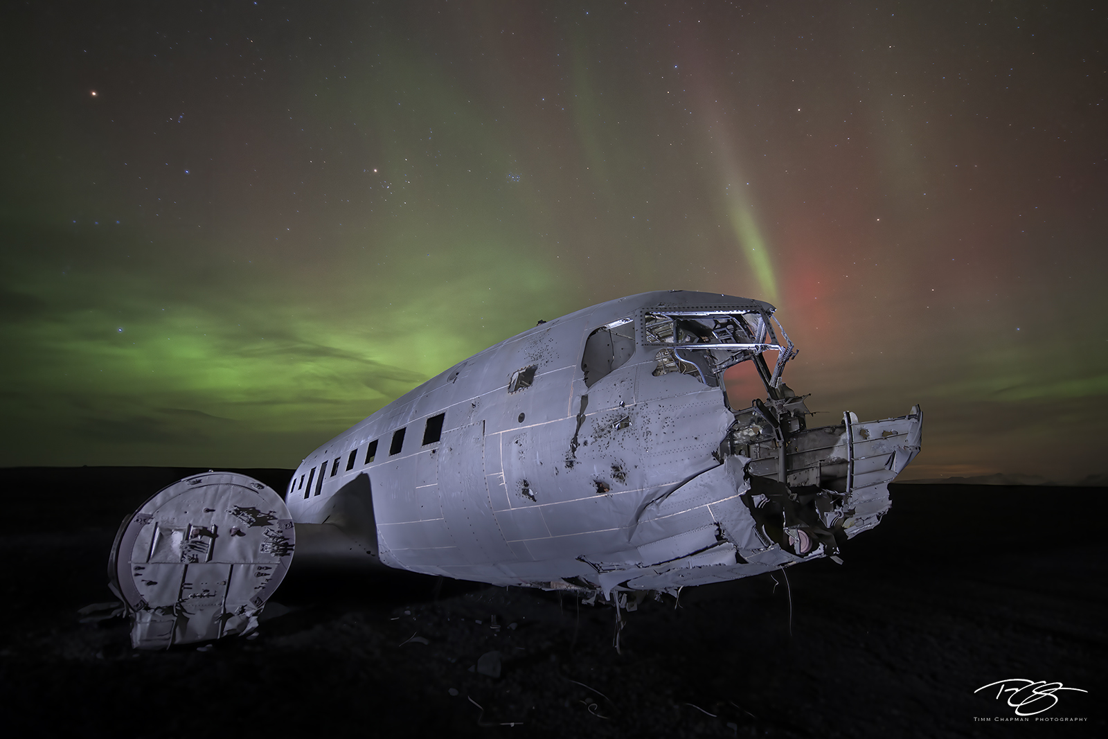 The Aurora Borealis dances above the corpse of a downed Dakota aircraft on a barren expanse in Southern Iceland
