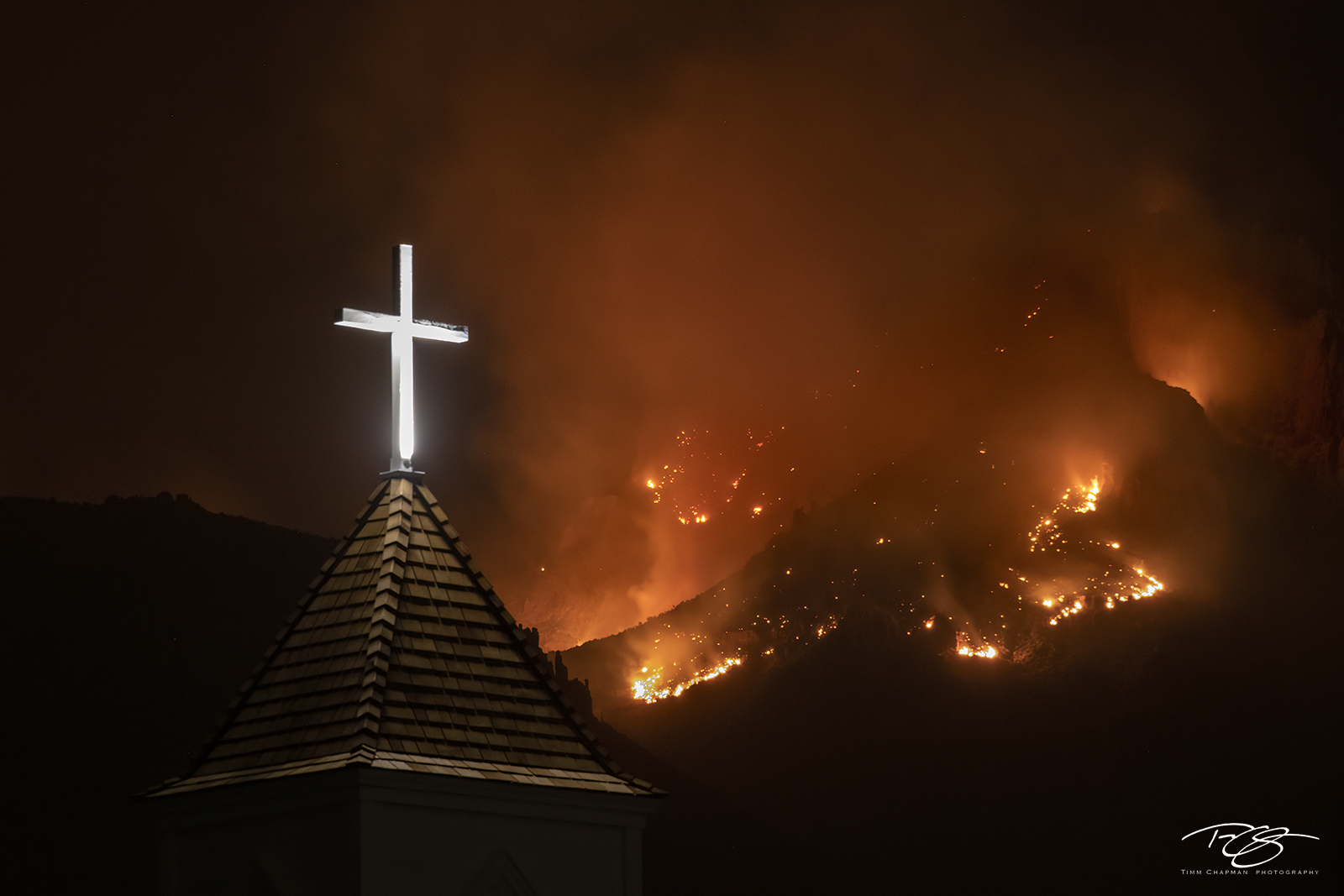 A raging forest fire on Superstition Mountain contrasts with the glowing cross from a nearby Chapel