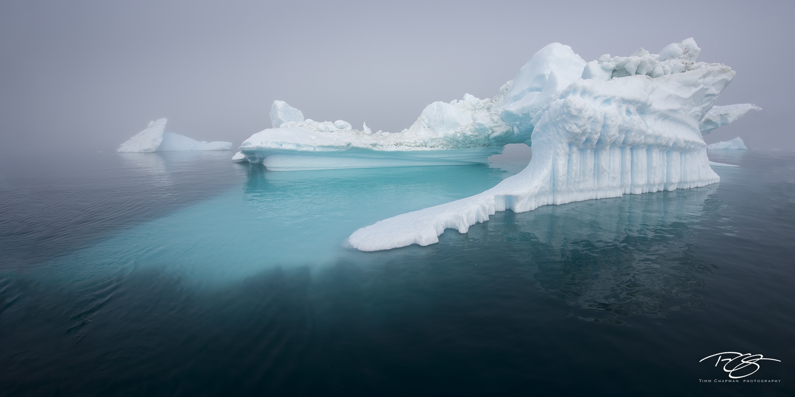 A massive sculpted iceberg appears through the thick fog cloaking Disko Bay
