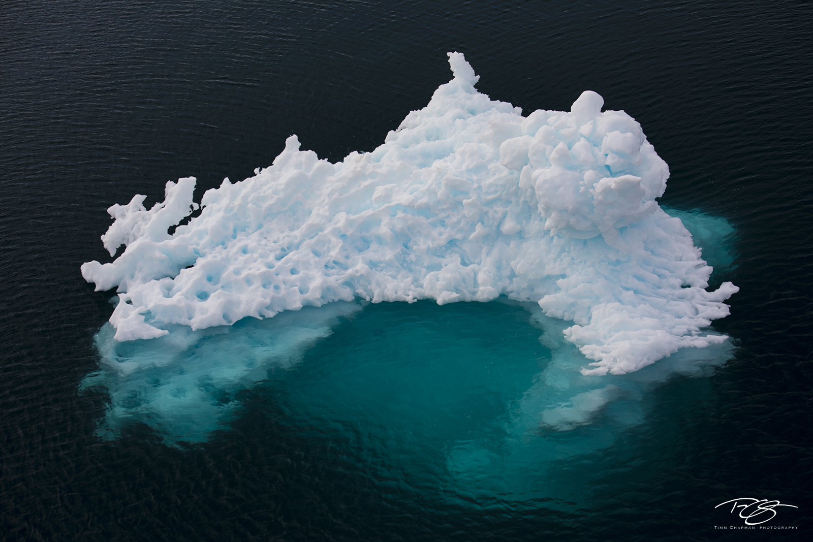 Wind and weather carefully sculpt an iceberg in the Scoresbysund of East Greenland