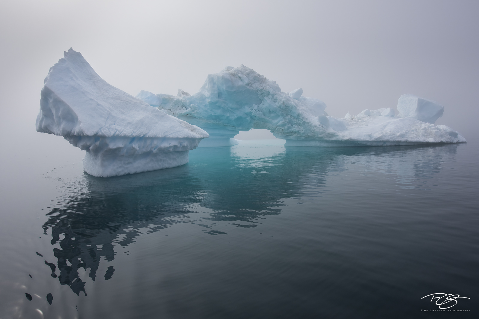 A spectacularly sculpted iceberg emerges from the thick fog covering West Greenland's Disko Bay