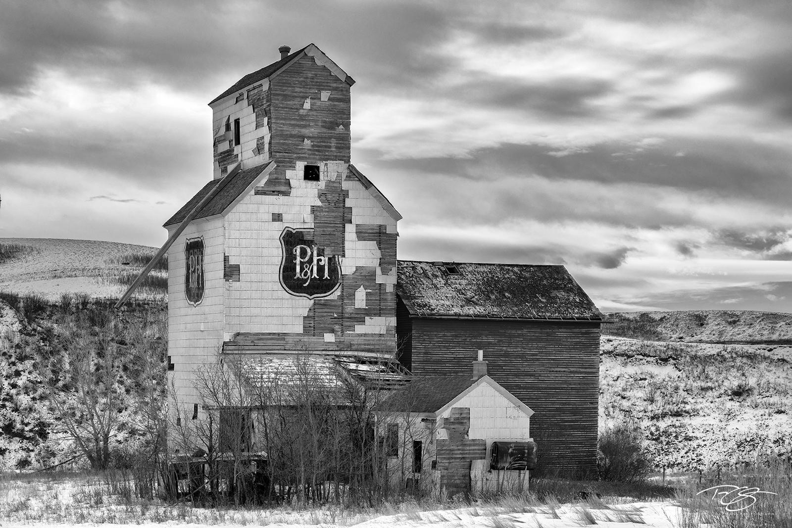 A near century old Parrish & Heimbecker grain elevator slowly succumbs to the harsh prairie winter