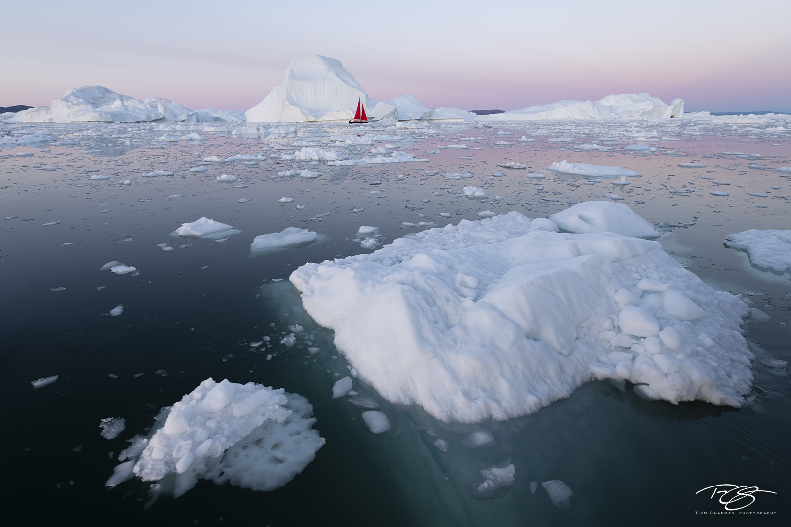 A sailboat navigates through the melting masses of ice being calved from the Jakobshavn glacier in West Greenland
