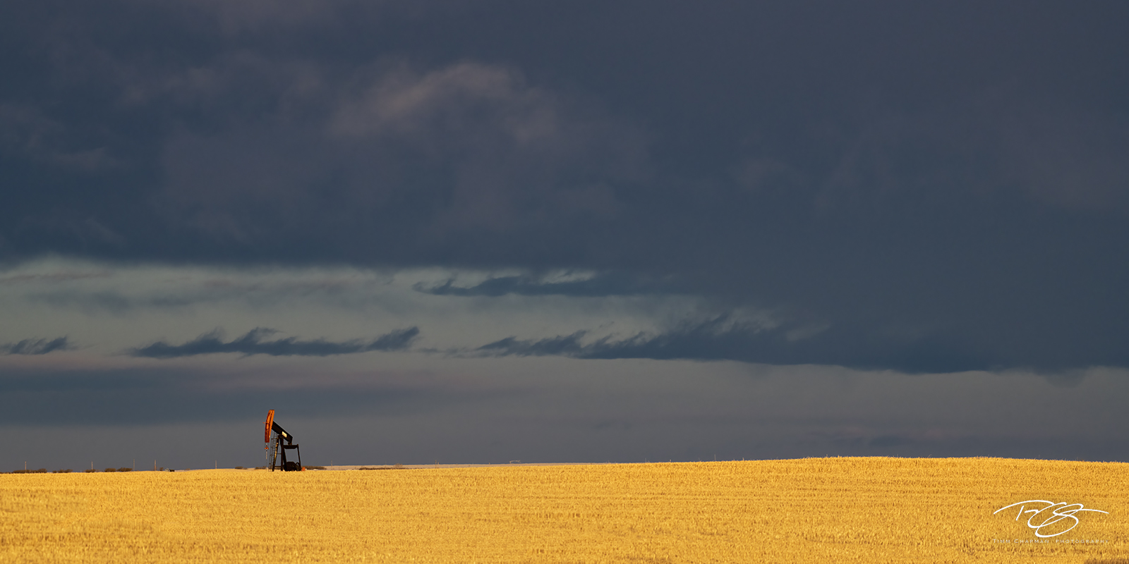 A lone pump jack mines for hydrocarbons beneath a threatening sky