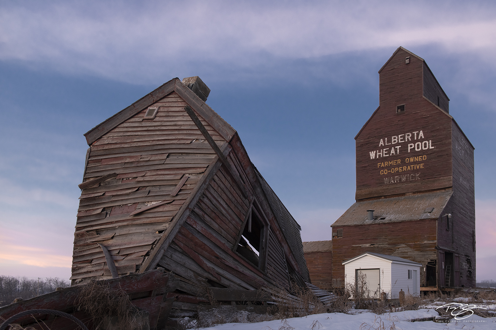 Retired since 1979, a near century-old grain elevator watches as it's neighbour succumbs to gravity