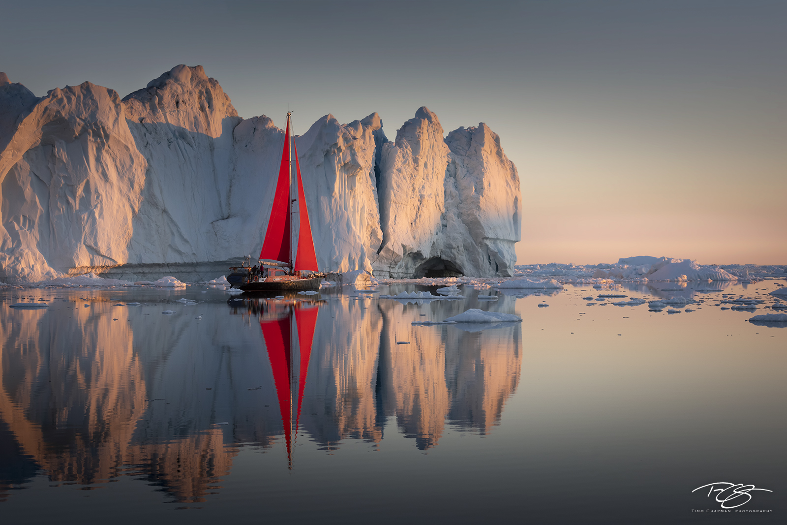 Kangia icefjord; ice; iceberg; disko bay; dawn; sunrise; early morning; icefjord; ship; sailboat; sailing; red sails; schooner; scarlet sails; yacht, reflection; golden light; golden hour; pastel sky, photo