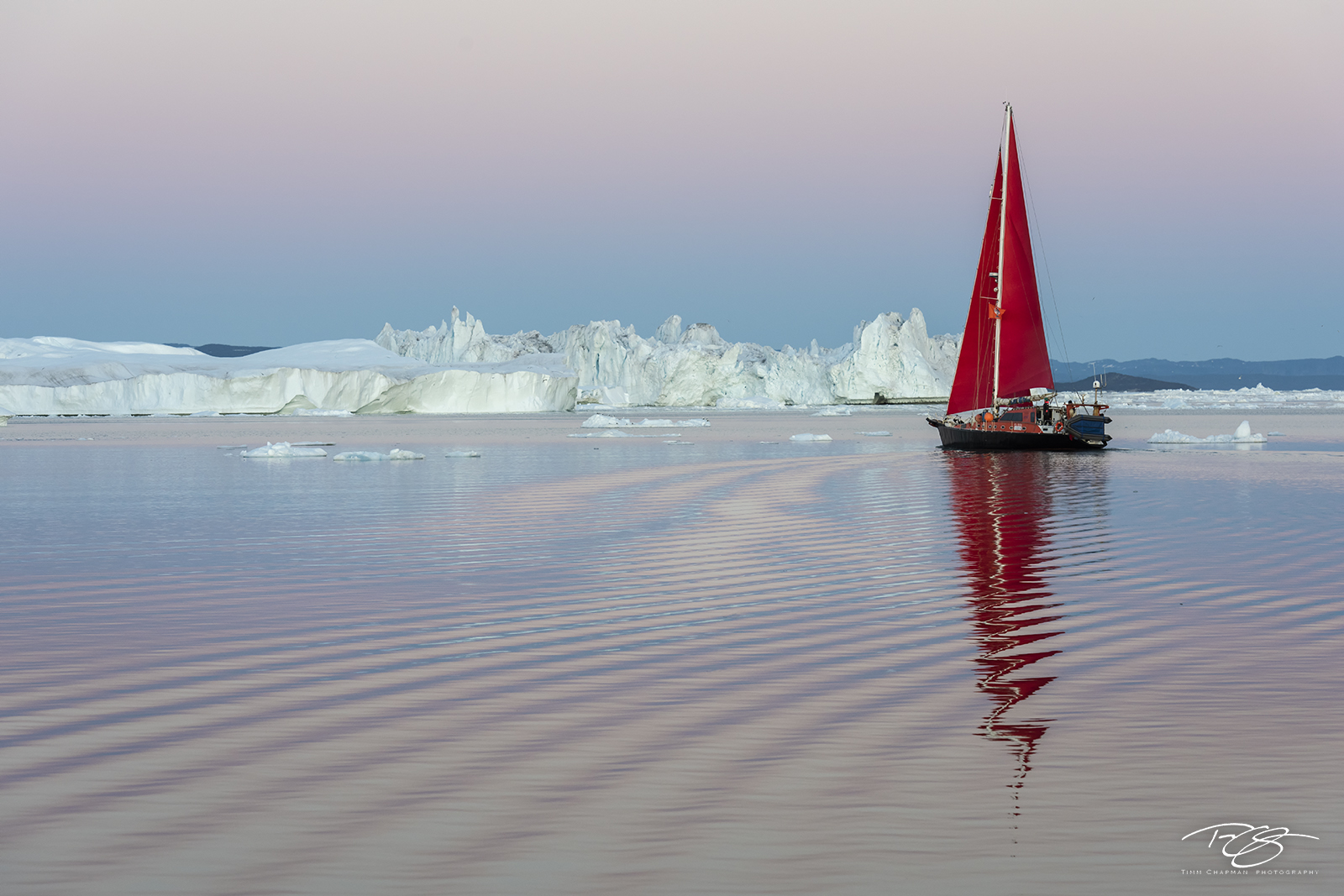 Kangia icefjord; ice; iceberg; disko bay; predawn; dusk; eventide; twilight; icefjord; ship; sailboat; sailing; red sails; schooner; scarlet sails; swizzle, reflection, pastel sky; pink; blue; scarlet, photo