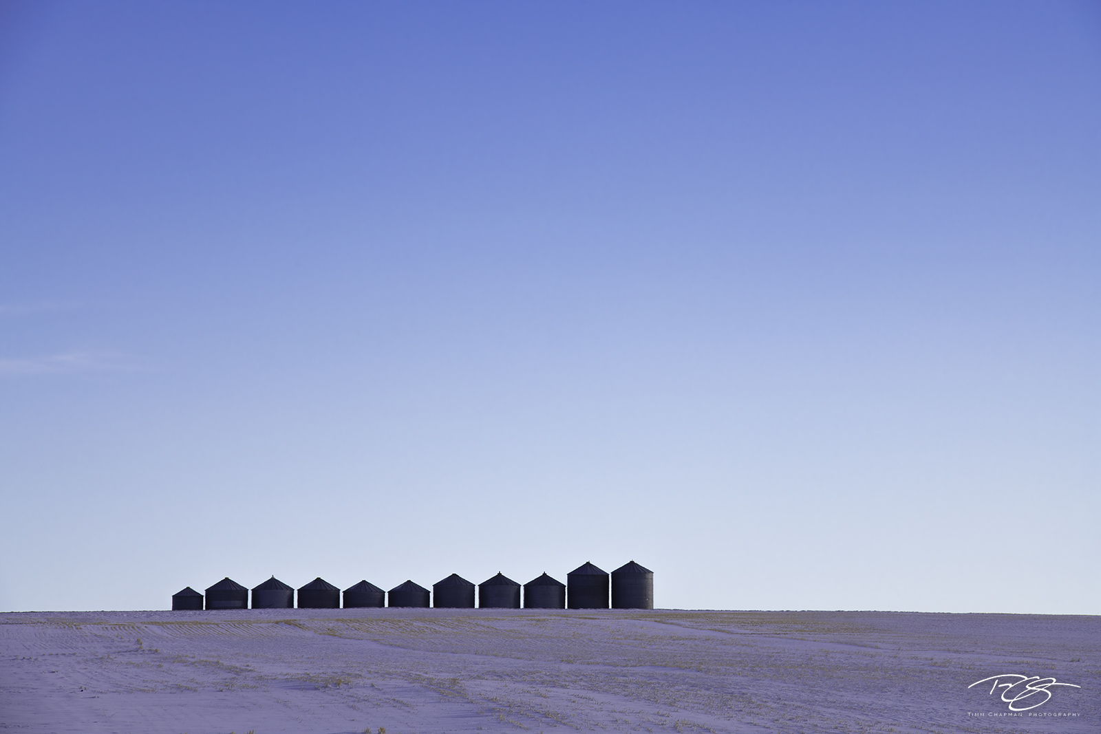 A line of silos stand shoulder to shoulder beneath the grand canopy of the prairie sky