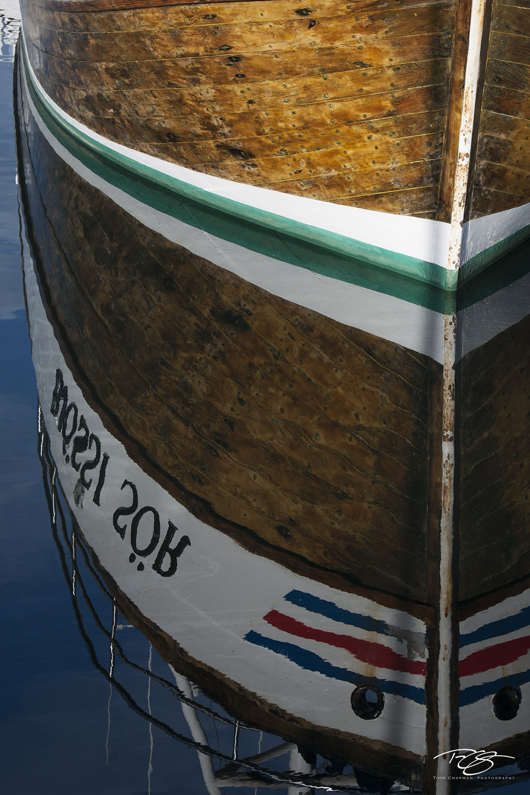 The bow of a Scandinavian ship reflects in the harbour in Husavik