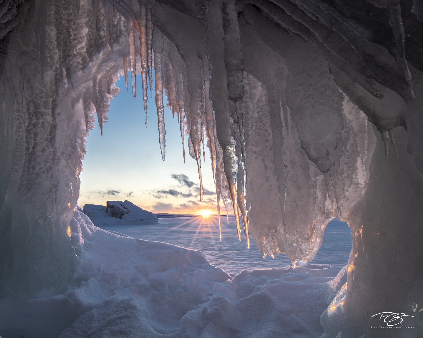 The setting sun casts its last warm rays into an ice cave