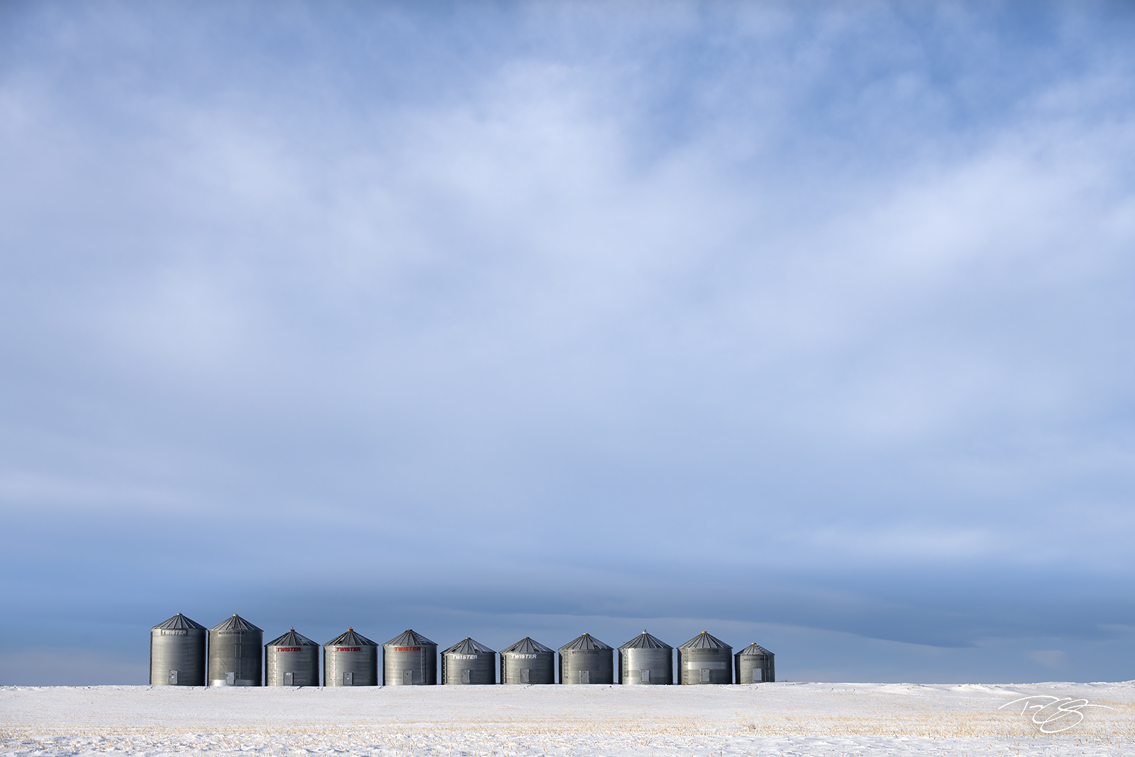 A line of silos stand quietlu beneath the grand canopy of the prairie sky