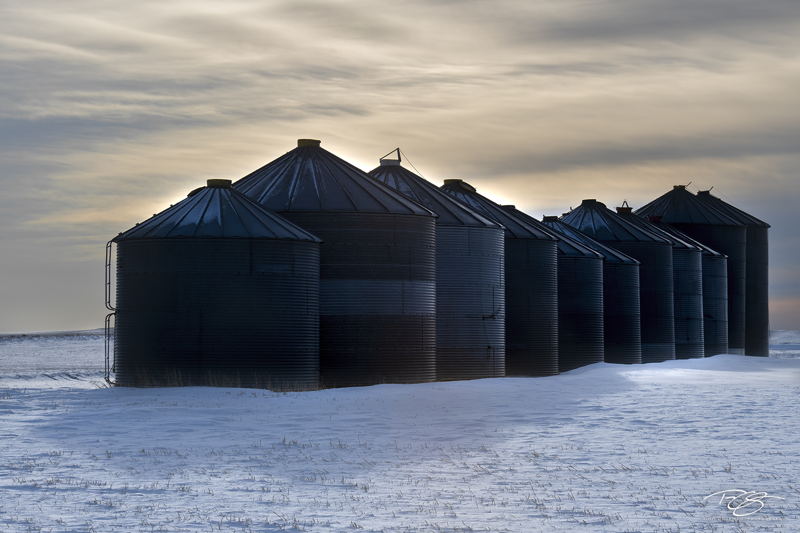 A long line of grain silos huddle together for warmth under the cold, brooding winter sky
