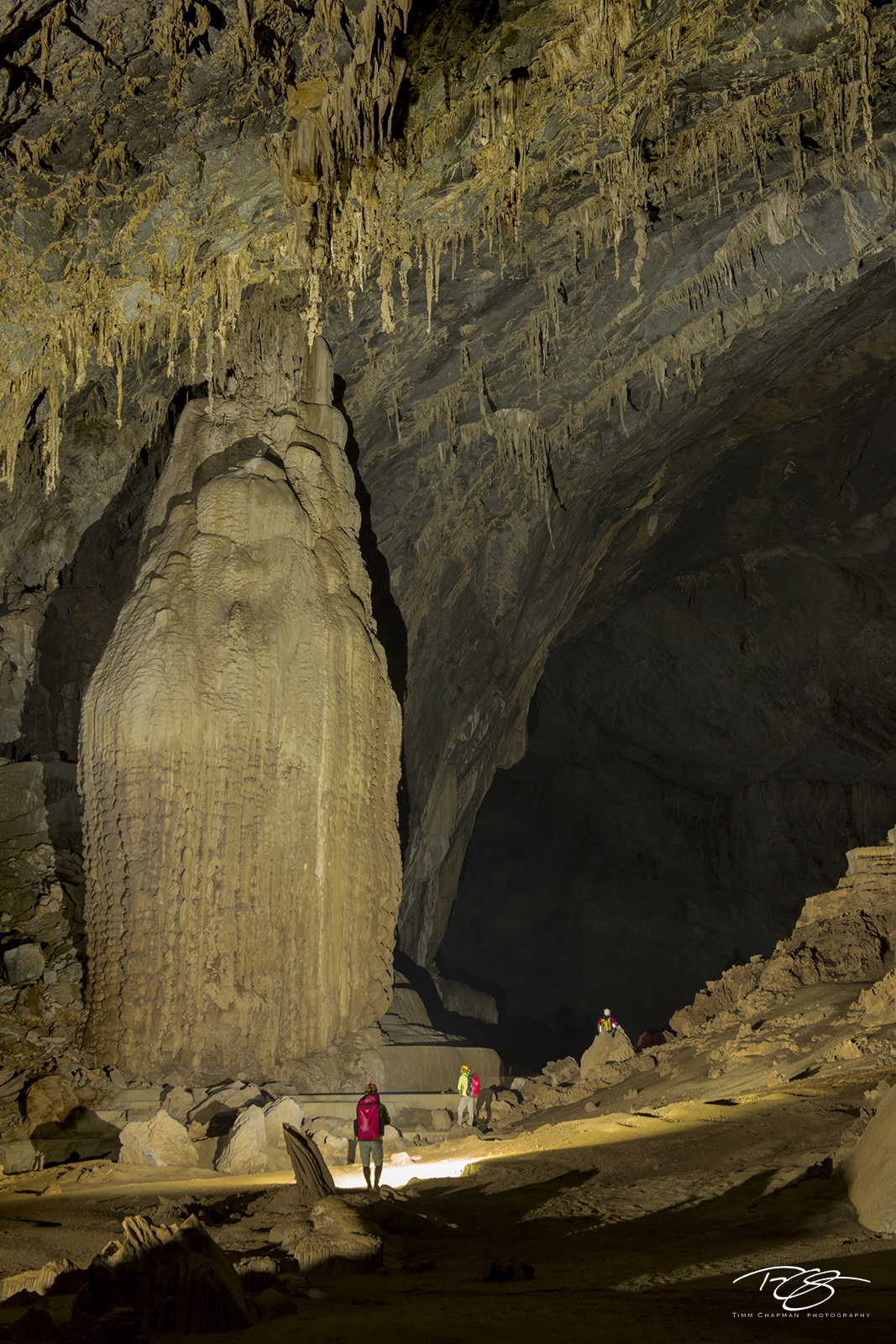 Cave explorers pass by an enormous stalactite inside Hang Én cave