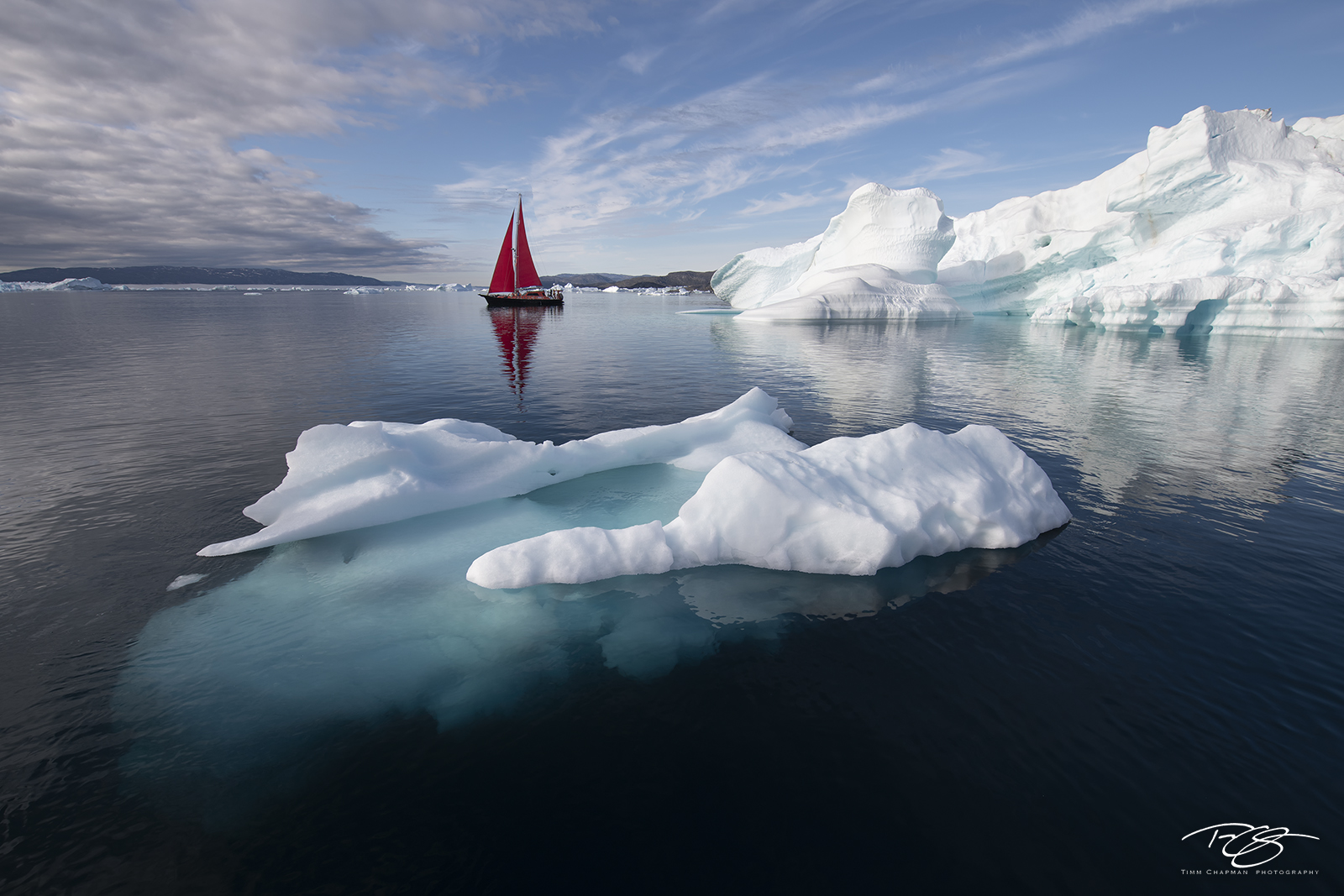 reflection; cloudy; blue; ice visible underwater; iceberg visible underwater; scarlet sails, ice; iceberg; disko bay, sailboat; sailing; schooner; red sails, photo