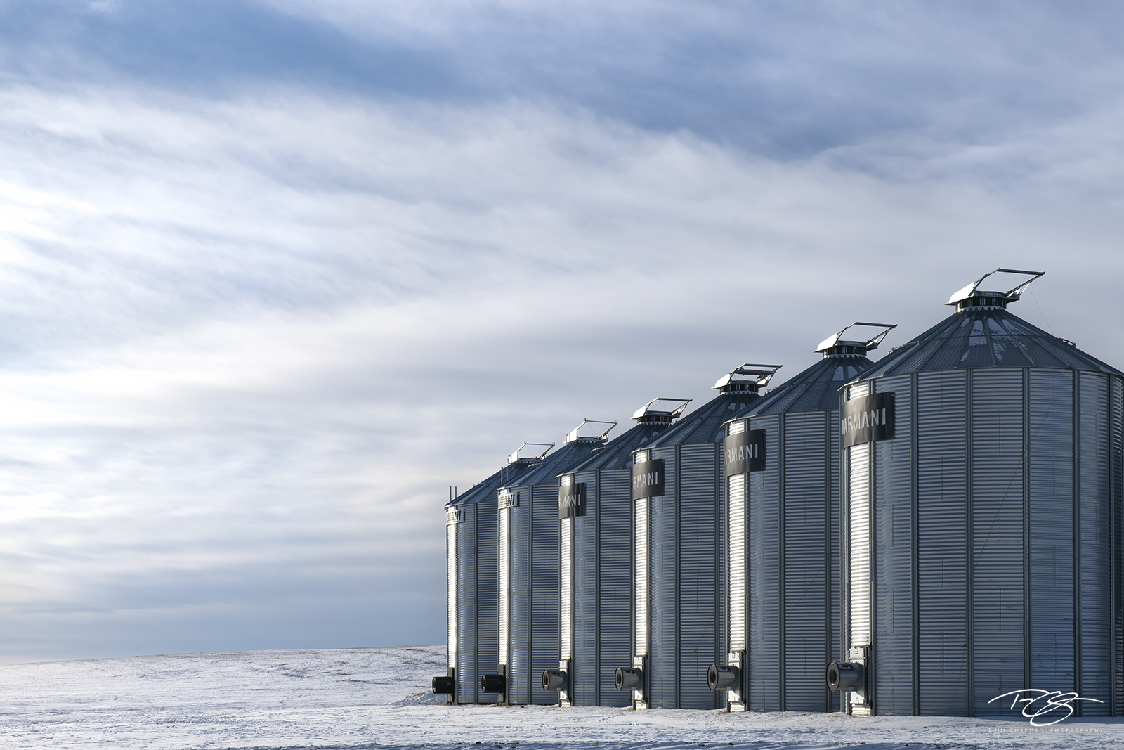 A stand of (D)Armani Silos stand shoulder to shoulder under the cold prairie sky